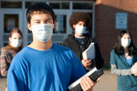 Shot for stock photography. Four teens of various ethnic backgrounds in front of a school wearing masks to protect against germs holding books.