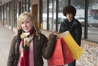 Shot for stock photography. A teenage girl with shopping bags smiles at the camera while a teenage boy looks on.